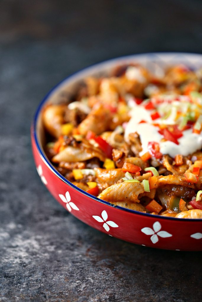 Slow cooker taco pasta in a multi-coloured pasta bowl with lots of garnish on top.