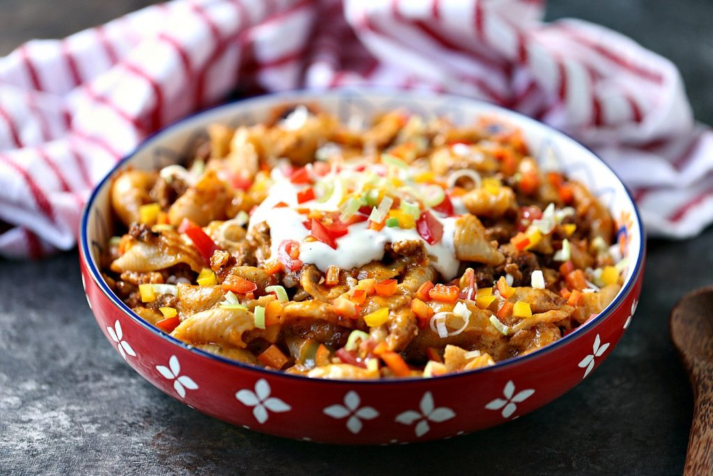Slow cooker taco pasta in a mutli-coloured pasta bowl with a red and white napkin in the background.