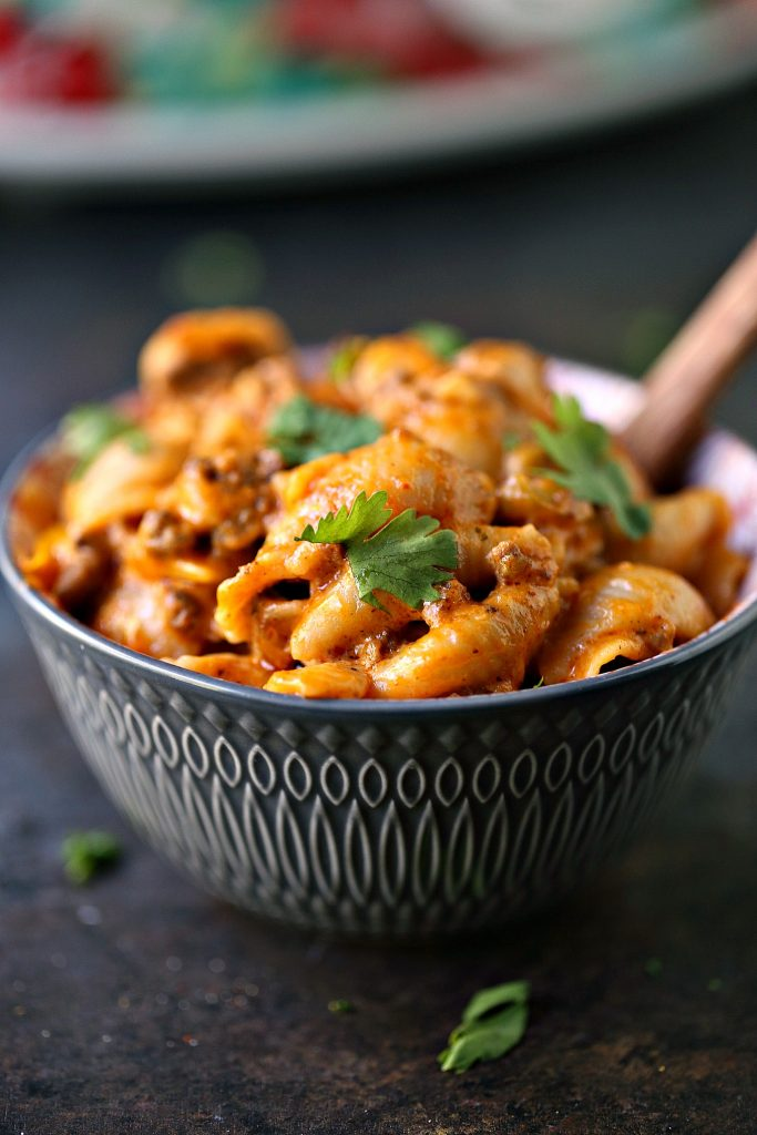 Slow Cooker Taco Pasta in s grey bowl with a wooden spoon in it.