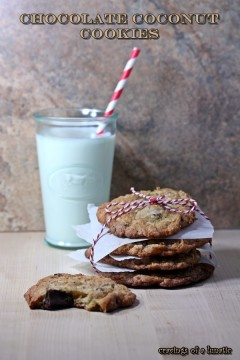Coconut Chocolate Cookies stacked on a counter with one cookie with a bite out and a glass of milk in the background