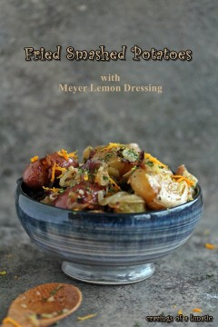 Fried Smashed Potatoes with Meyer Lemon Dressing in a blue bowl on a counter