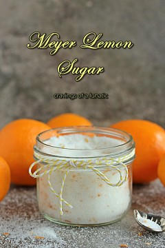 meyer lemon sugar stored in a mason jar, spoon resting on counter and meyer lemons are in the background