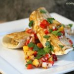 asian inspired enchiladas with chicken, quinoa and peach salsa piled on a white plate and topped with peach salsa