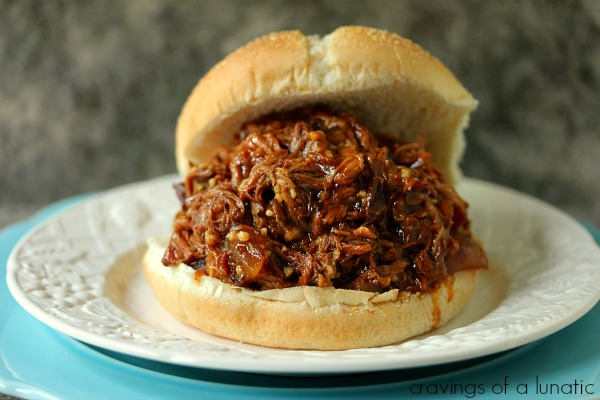 Slow Cooker Root Beer Pulled Pork served on a white plate stacked on a blue plate.