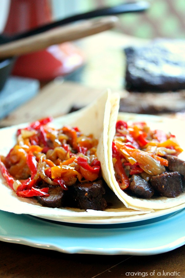 fajitas piled on tortillas on a blue and white plate