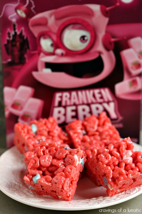 Franken Berry Krispies on a white plate with a box of the monster cereal behind it
