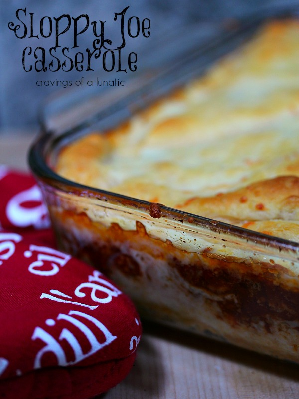 Sloppy Joe Casserole baked in a clear pyrex baking dish with a red oven mitt nearby