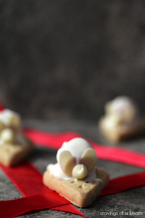 Shortbread Christmas Mice on a dark counter with red ribbon on it