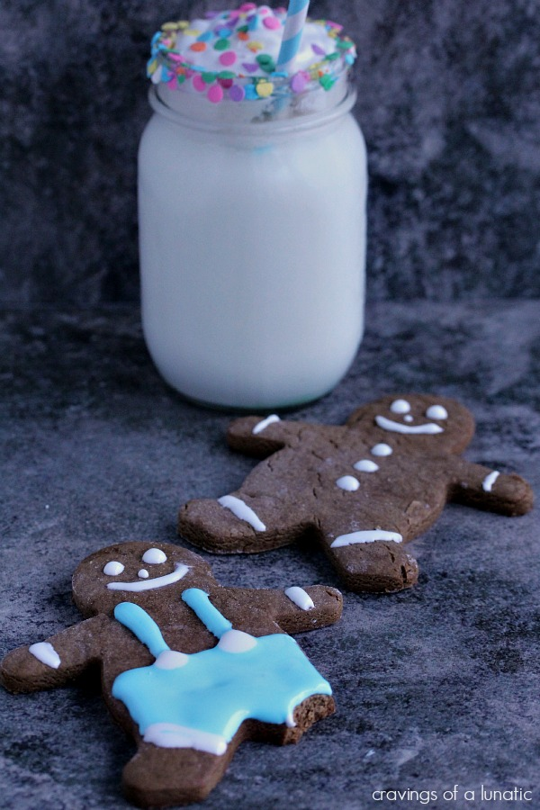 gingerbread people decorated on a dark counter with a glass of milk nearby