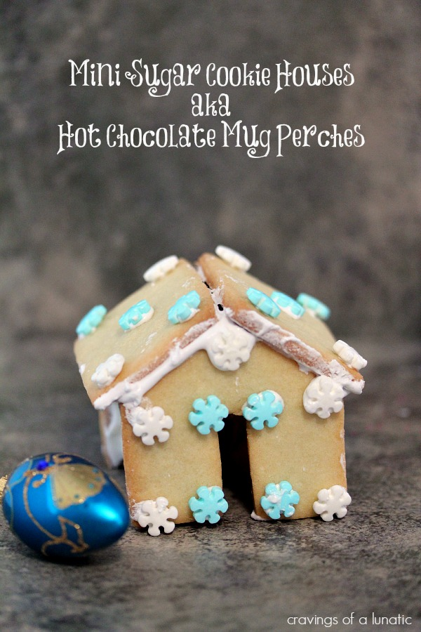 Mini Sugar Cookie Houses Hot Chocolate Mug Perches on a dark counter.