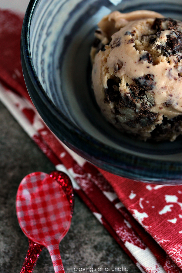 Chunky Turtle Ice Cream in a blue bowl on a red and white napkin with red spoons nearby.