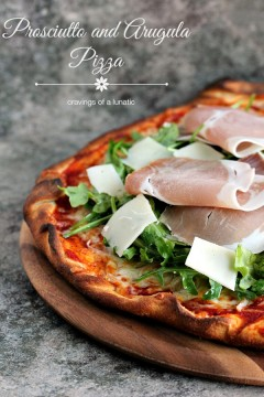 Pizza topped with sauce, cheese, arugula and prosciutto served on a wood board.