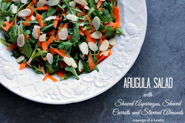 Arugula Salad with Shaved Carrots, Shaved Asparagus and Almonds served in a white bowl.