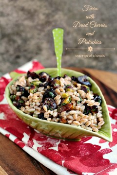 Farro with Pistachios and Dried Cherries served in a green leaf shaped bowl on a red and white napkin.
