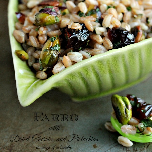 Farro with Pistachios and Dried Cherries served in a green bowl shaped like a leaf with a green spoon on a dark counter.