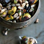 Farro with Pistachios and Dried Cherries served in a silver bowl on a dark counter.