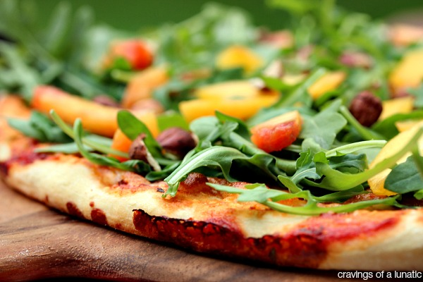 Amazing Pizza layered with Arugula, Fresh Peaches, and Chopped Hazelnuts. This recipe is a real crowd pleaser and perfect for summer!