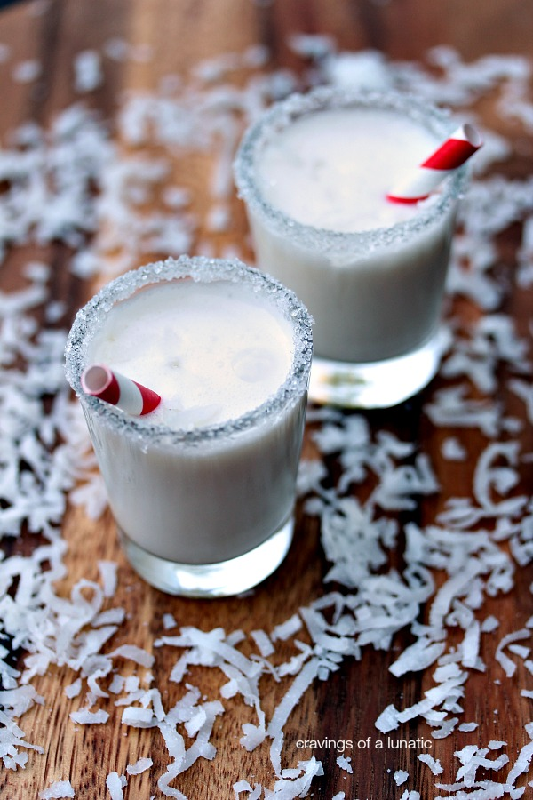 Mini Coconut Milkshakes served in shot glasses with decorative rims and tiny straws inside. Grated coconut is scattered on a wood tray around the milkshakes.