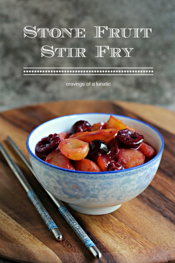Stone fruit stir fry served in a blue and white bowl with chopsticks on a wood board.