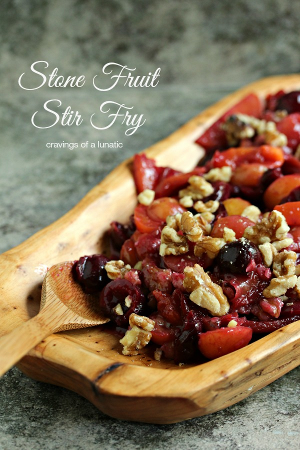 Stone fruit stir fry cooked to perfection and served in a wooden dish with a wooden spoon.