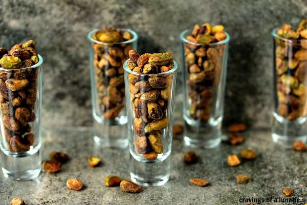 Toasted pistachios in shot glasses on a dark surface.