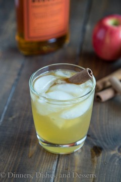 Bourbon Apple Cider in a glass with ice and a cinnamon stick. Glass is on a wood board with ingredients in the background.