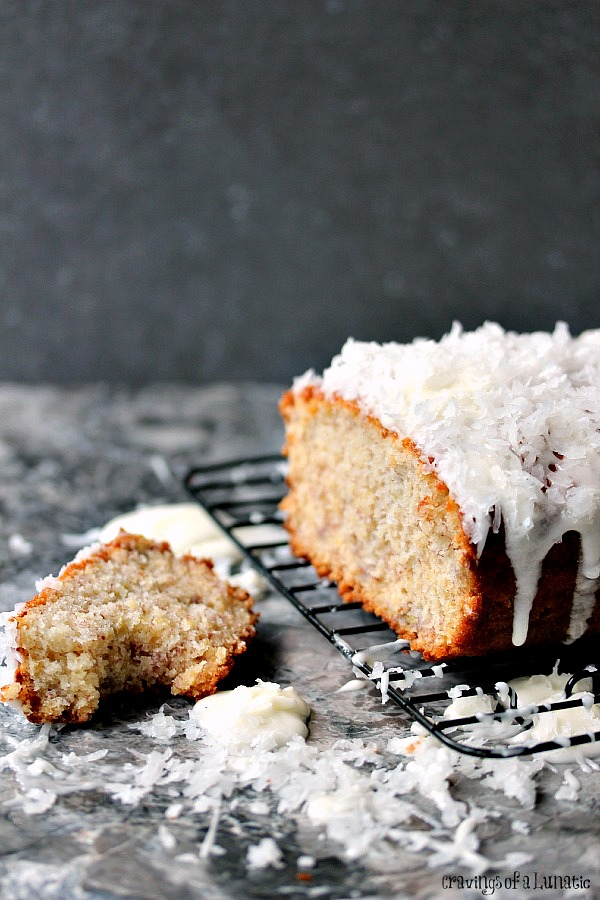 Banana Coconut Sweet Bread sliced with lots of icing and coconut scattered around.