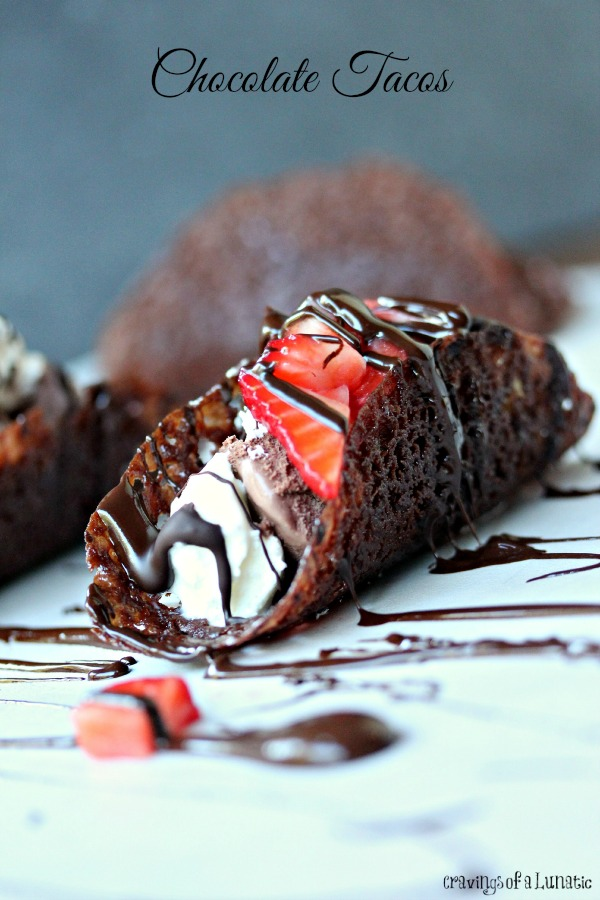 Chocolate tacos filled with ice cream, whipped cream, strawberries and chocolate sauce.