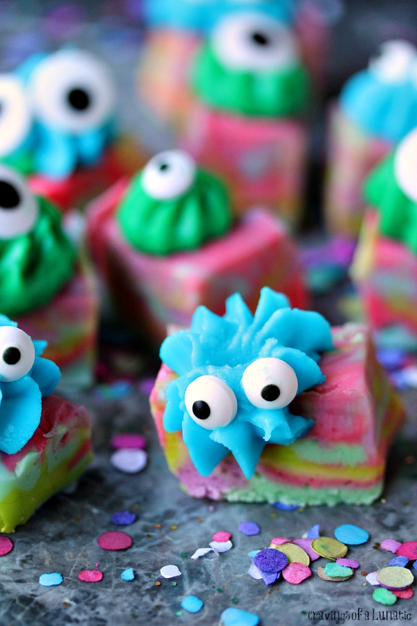 Easy Monster Fudge is brightly coloured swirled fudge cut into squares then topped with icing and googly eyes. Fudge is sitting a grey counter with colourful confetti all around it.