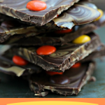 Peanut Butter and Chocolate Bark with Reese's Pieces stacked on a dark counter.