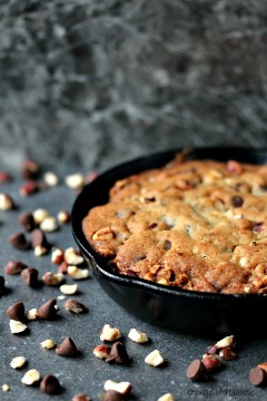 Chocolate Hazelnut Skillet Cookie on a dark counter with ingredients spilled all over it.