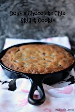 skillet cookie cookie cooling on the counter on top of a white, black and pink tea towel