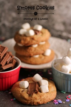 S'mores Cookies on a white plate with one cookie on the counter in front of it. A small red bowl is holding chocolate and a small blue bowl is holding mini marshmallows.
