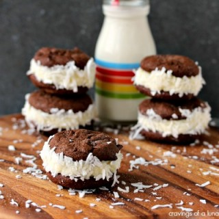 Coconut Filled Sandwich Cookies | This recipes is incredibly easy to make. Fluffy coconut filling wedged between chocolate cookies, then dunked in more coconut. This recipes is for all you serious coconut lovers out there.