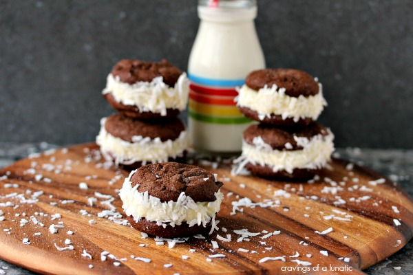 Coconut Filled Sandwich Cookies on a wood board with coconut scattered around, and a small jar of milk in the background.