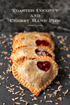 Toasted Coconut and Cherry Hand Pies stacked on a dark counter with toasted coconut scattered around them.