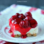 No Bake Cherry Cheesecake Bars served on a white plate on a red and white napkin.