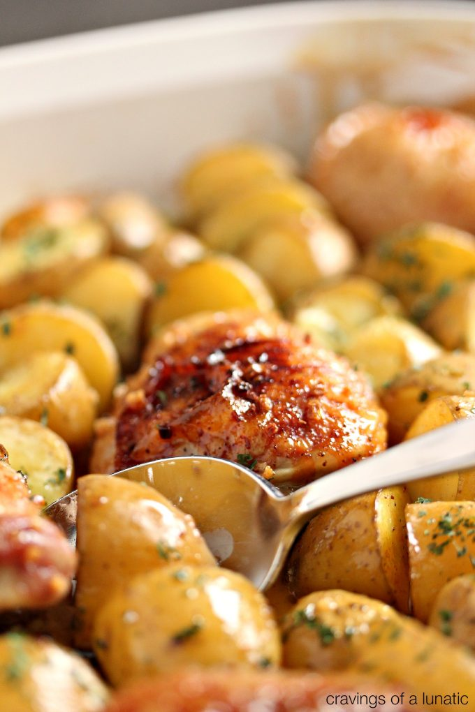 Honey Baked Chicken and Potatoes in a white pan with a serving spoon scooping out some potatoes