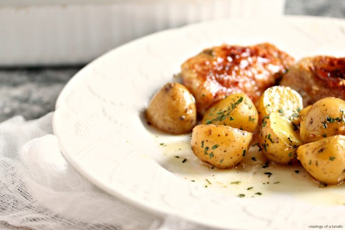 Honey Baked Chicken and Potatoes on a white plate with serving dish in the background