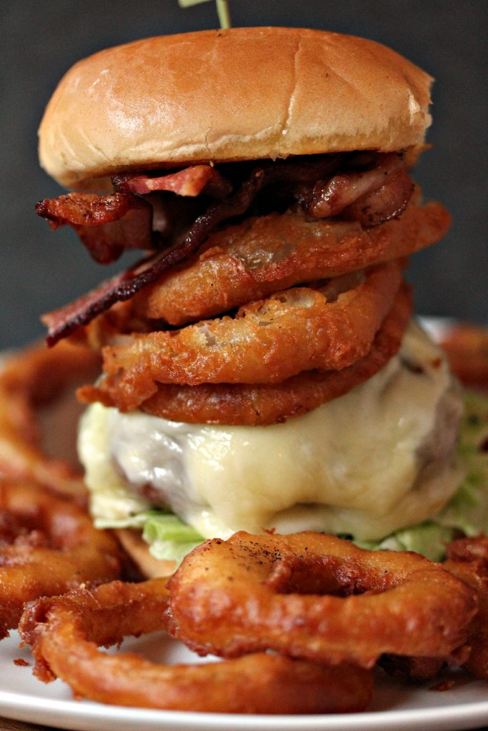Onion Ring Cheeseburger- This burger is cooked on a plank, then topped with mozzarella cheese, provolone cheese, onion rings and bacon. My hubby has dubbed it The Ringer.