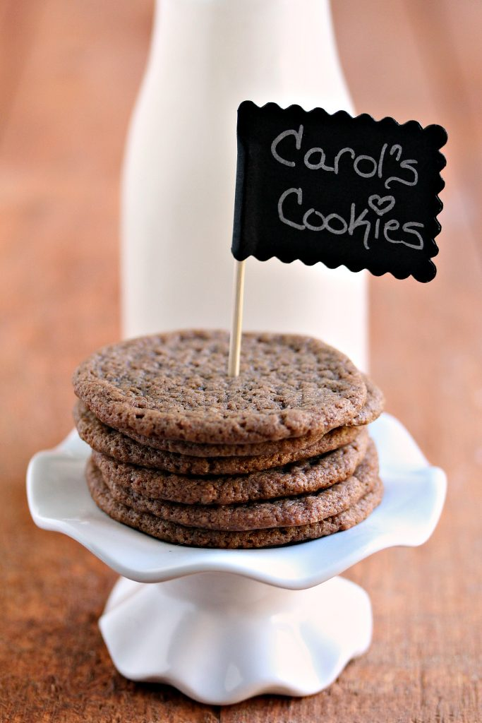 Chewy chocolate cookies stacked on a mini cupcake stand with a tiny chalkboard stuck in them that has the recipe name written on it, with a bottle of milk in the background.