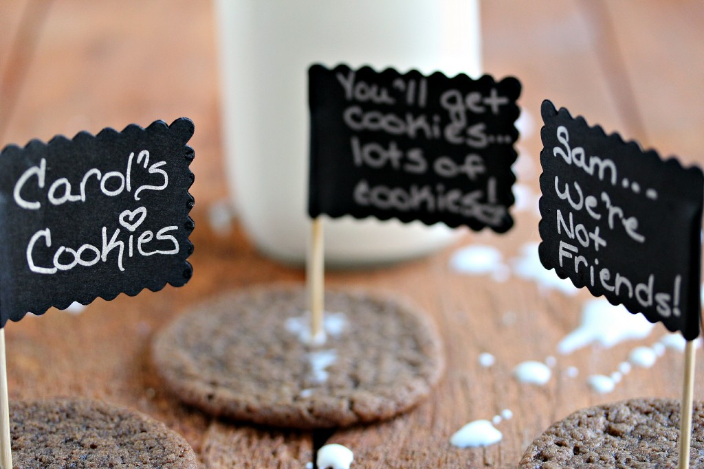 Chocolate cookies with tiny signs on them and a jar of milk in the background.