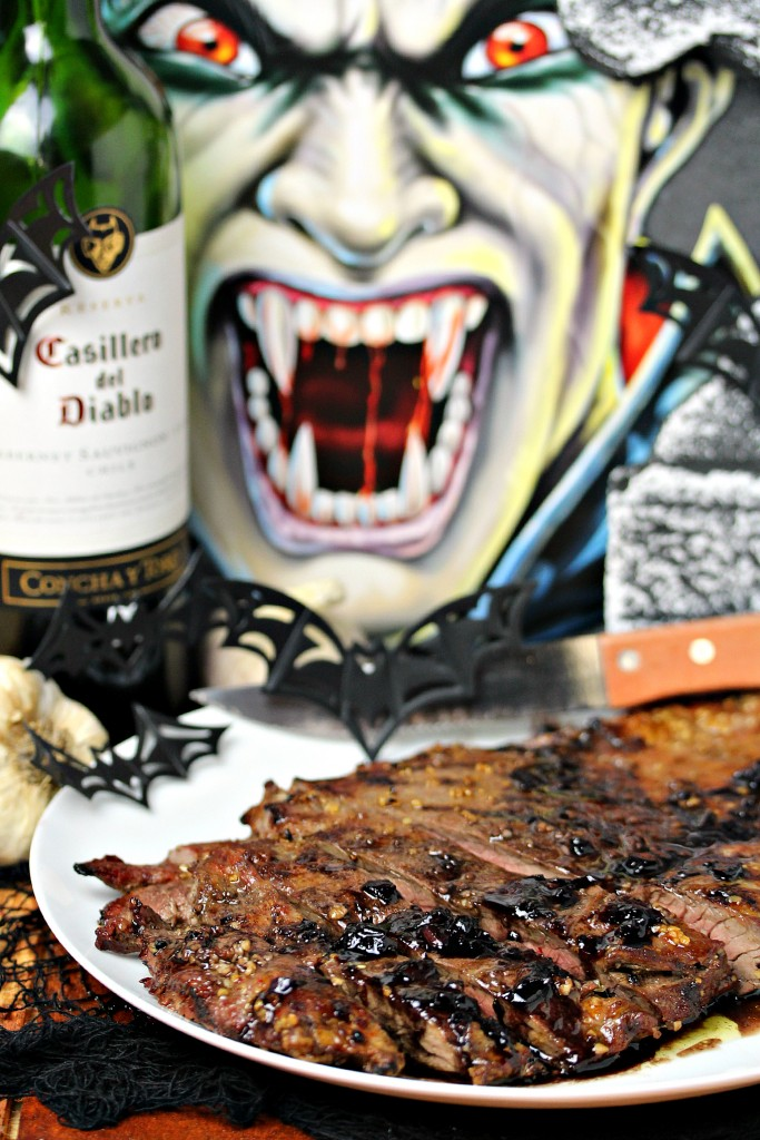 vampire steaks on a white plate with wine and a photo of a vampire behind it