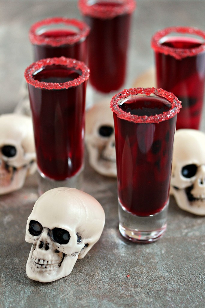 walker blood sangria served in shot glasses, tiny plastic skulls are scattered around them