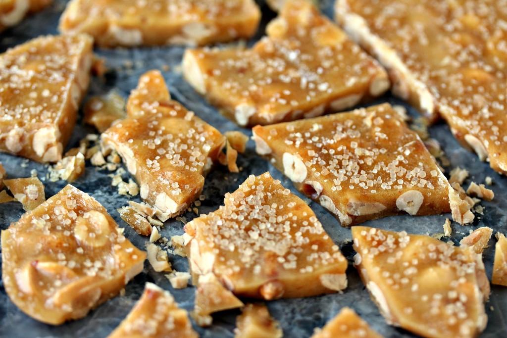 Microwave Peanut Brittle broken into pieces on a dark counter.