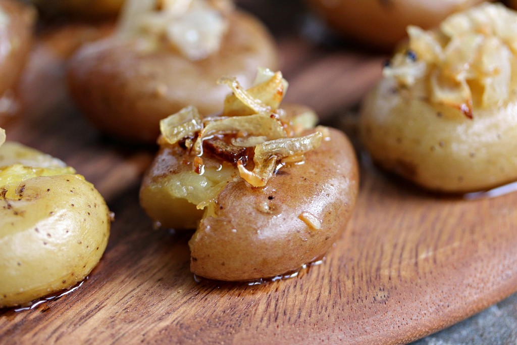 Smashed Potatoes with Onions and Garlic on a wooden serving board.