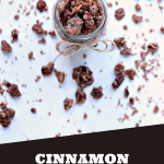 Cinnamon Pecans in a mason jar on a white surface with pecans scattered about.