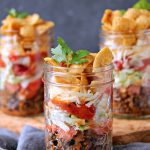 Mini Fritos Taco Salads layered in mason jars sitting on a wood platter on a tabletop