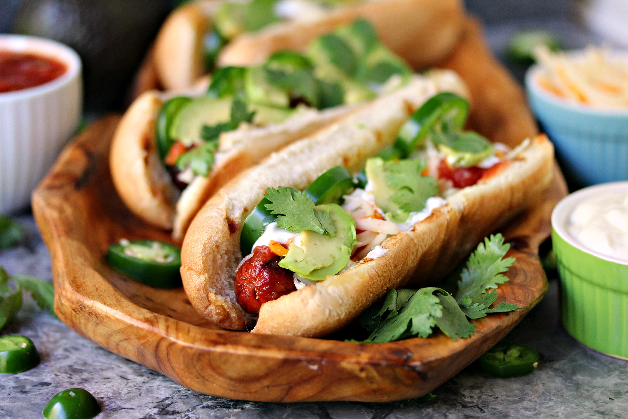 Mexican Hot Dogs from cravingsofalunatic.com- These hot dogs are grilled to perfection, then topped with jalapeno peppers, salsa, cheese, sour cream and avocados. This recipe is a real crowd pleaser. (@CravingsLunatic)