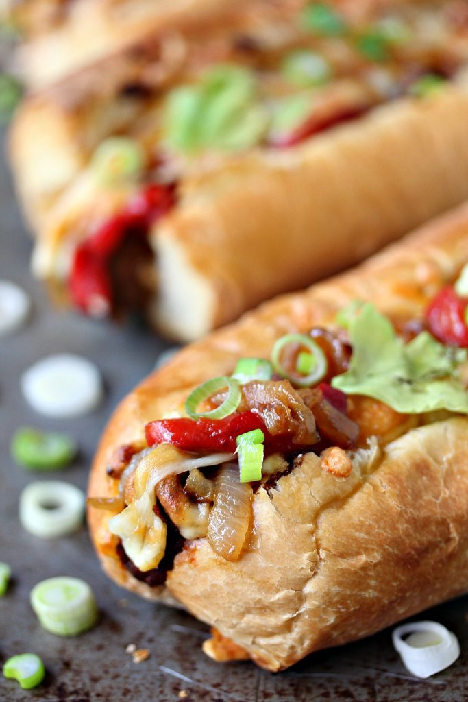 close up image of tex-mex meatball subs with onions, roasted red peppers and cheese overflowing from the edges